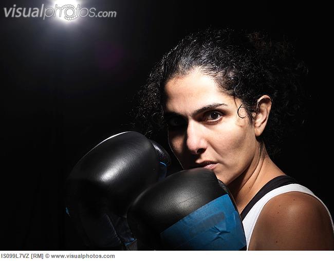 Portrait of female boxer against black background